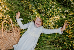 happy little girl in a cotton dress lies in a field of daisies in the summer at sunset. laughs, view from above