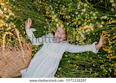 happy little girl in a cotton dress lies in a field of daisies in the summer at sunset. laughs, view from above Stockfoto ©