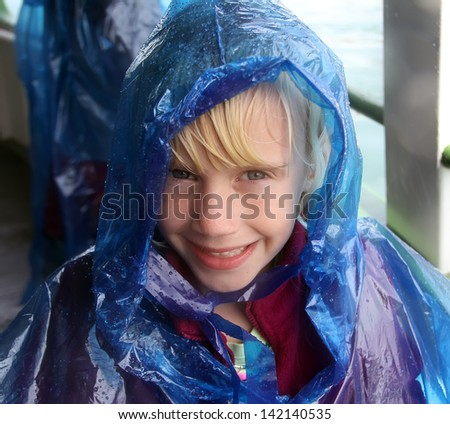 Happy little girl in blue raincoat. Niagara Falls boat trip.
