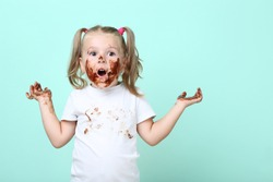 Happy little girl in chocolate on mint background