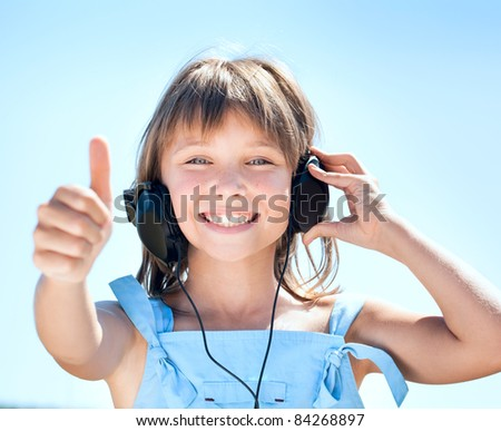 Happy little girl in headphones listens to music against the blue sky