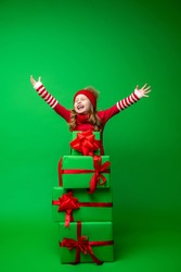 happy little girl in red hat plays with pyramid Christmas gift boxes on green background in Studio. child is happy to close his eyes and raise his hands up, gets lot gifts for Christmas. Advertising.