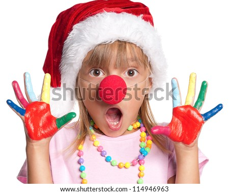 Happy little girl in Santa hat with paints on hands and red clown nose isolated on white background
