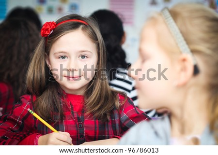 Happy little girl in school with her friends arround