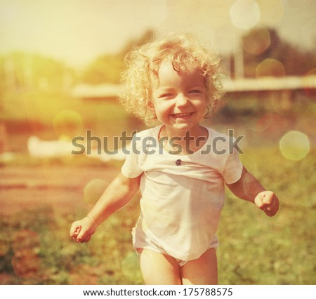 Happy little girl in summer sunlight. Vintage paper textured