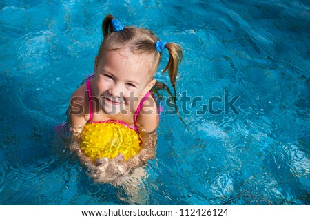 happy little girl in the pool with ball