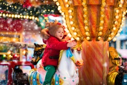 Happy little girl in warm red jacket and knitted reindeer hat riding carousel horse during family trip to traditional German Christmas market. Kids at Xmas outdoor fair on snowy winter day.