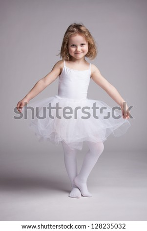 Happy little girl in white dress ballerina