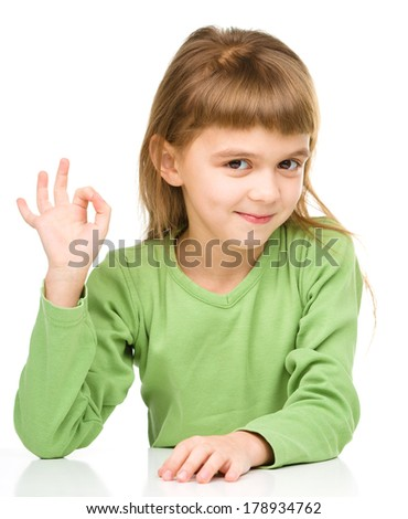 Happy little girl is showing OK sign, isolated over white