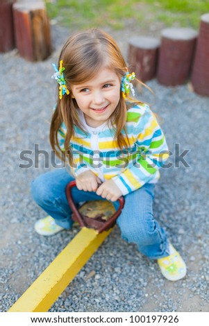 Happy little girl is swinging on playground