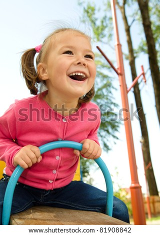 Happy little girl is swinging on see-saw