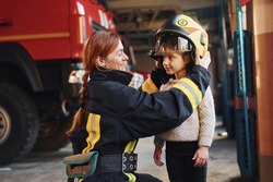 Happy little girl is with female firefighter in protective uniform.