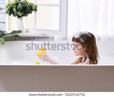 Happy little girl kid sitting in bath tub  in the bathroom. Portrait of baby bathing in a bath full of foam near window