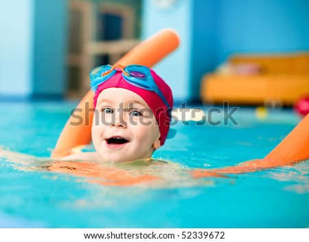Happy little girl learning to swim with pool noodle
