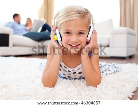 Happy little girl listening music lying on the floor in the living-room