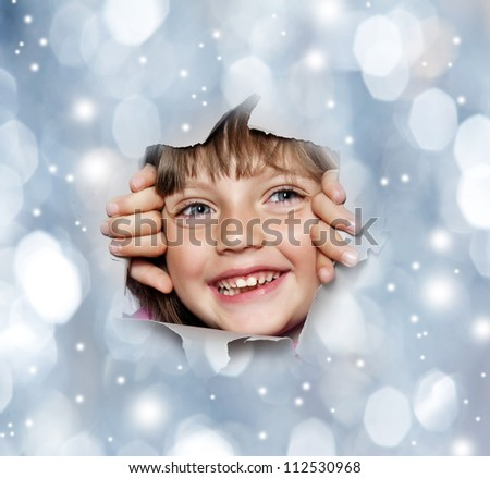 happy little girl looking out of a hole in christmas background