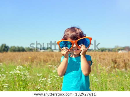 Happy little girl looking  through a big sunglasses