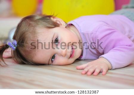 Happy little girl lying on the floor