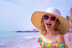 Happy little girl makes a funny grimace and shows her tongue. Adorable girl in a big straw hat, sun glasses and in a swimsuit relaxing on the beach near sea. Cute child on vacation looks at the sea.