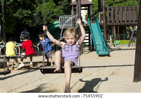 Happy little girl on playground swinging