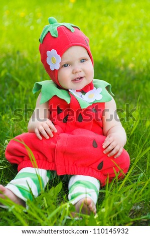Happy little girl  on the meadow in a strawberry costume