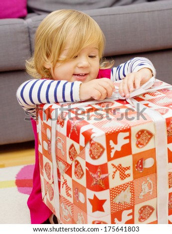 Happy little girl opens a Christmas gift at home. - stock photo
