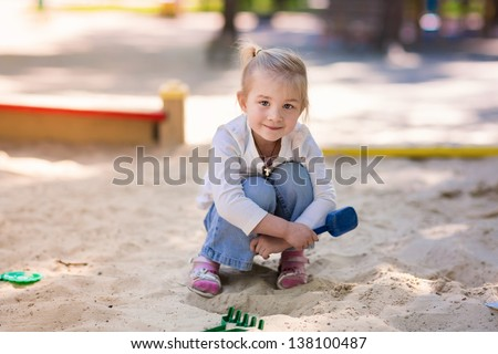 Happy little girl playing in a sandbox on the playground