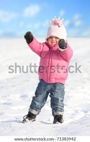 Happy little girl playing in a snowy landscape.