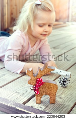 Happy little girl playing with Christmas decorations - reindeer and cones. Natural lighting setting.