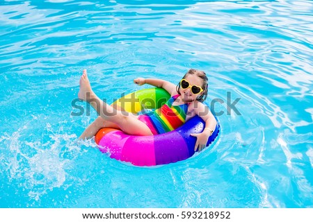 Happy little girl playing with colorful inflatable ring in outdoor swimming pool on hot summer day. Kids learn to swim. Child water toys. Children play in tropical resort. Family beach vacation. #593218952