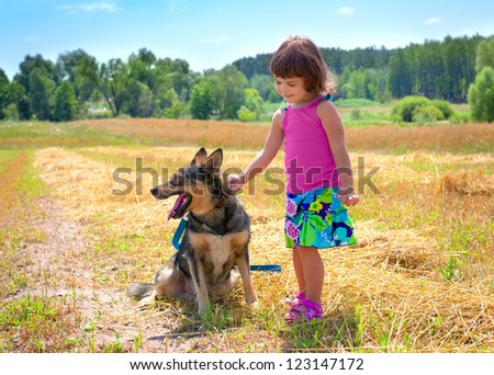 Happy little girl playing with dog