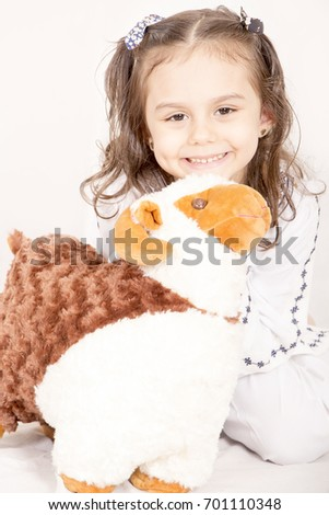 Happy little girl playing with her sheep toy - celebrating Eid ul Adha - Happy Sacrifice Feast #701110348