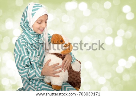 Happy little girl playing with her sheep toy - celebrating Eid ul Adha - Happy Sacrifice Feast #703039171