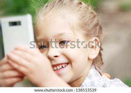 happy little girl playing with mobile phone camera in park