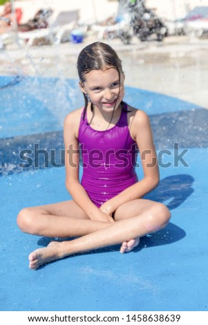 Happy little girl plays in aqua park, enjoying relaxing and splashing in water