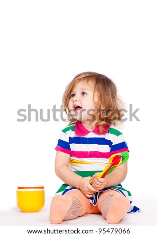 Happy little girl plays with cups and spoons