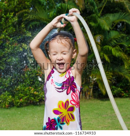 Happy little girl pours water from a hose
