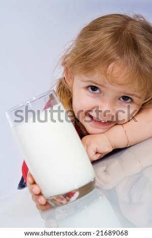 Happy little girl reaching for a glass of milk