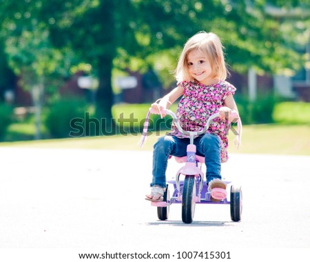 Happy Little Girl Riding a Tricycle Outside in Morning Light - Shutterstock ID 1007415301