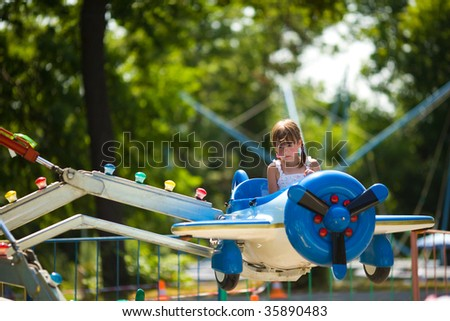 Happy little girl riding carousel in toy airplane