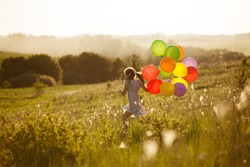 Happy little girl running across the field with balloons