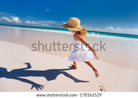 Happy little girl running and jumping at beach