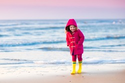 Happy little girl running and jumping in the waves on North Sea beach during winter vacation in Holland. Kids play in ocean sand dunes on cold autumn or spring day. Beach fun for family with children