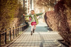 happy little girl running home from school