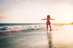 Happy little girl running inside water spreading her hands up on the beach - Baby having fun making splashing in the sea - Child, youth, happiness concept