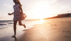 Happy little girl running on the beach at sunset - Kid having fun in holiday vacation with back sun light - Youth, lifestyle and happiness concept - Focus on silhouette