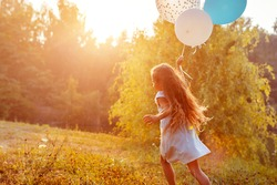 Happy little girl running with baloons in hand. Kid having fun in summer park at sunset. Outdoors activities