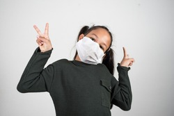 Happy little girl show v sign with hands, healthcare and infection control. Concept of positivism against the infection of the coronavirus, quarantine kids.
