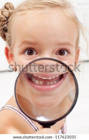 Happy little girl showing missing teeth through magnifier