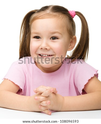 Happy little girl sits at a table and smile, isolated over white